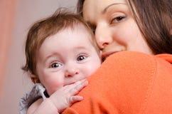 Bebé de seis meses en mamá feliz de las manos foto de archivo