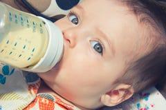 Bebé de siete meses adorable que come de la botella Fotos de archivo