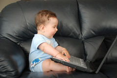Bebé de Smilling con la computadora portátil en un sofá Foto de archivo