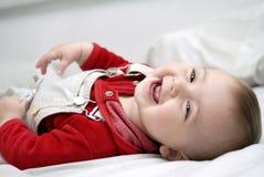Bebé de sorriso que coloca na cama Imagens de Stock