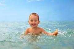 Bebé de sorriso que joga com água de mar Imagem de Stock