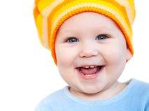 Bebé de sorriso que mostra os dentes que desgastam um chapéu Fotos de Stock Royalty Free