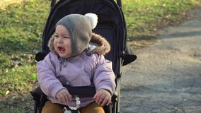 Bebé de Toddlr en el sombrero gris que se sienta en cochecito y el griterío Cochecito 4k del odio metrajes