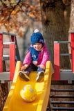 Bebé de tres años feliz en chaqueta en diapositiva Imágenes de archivo libres de regalías