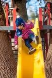 Bebé de tres años feliz en chaqueta en diapositiva Foto de archivo