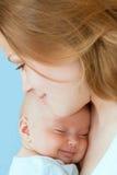Bebé de tres meses en sus manos de las madres. Foto de archivo