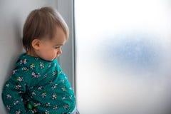 Bebé de un año caucásico lindo en la situación verde de la camisa con la parte posterior contra la pared al lado de la ventana br foto de archivo libre de regalías