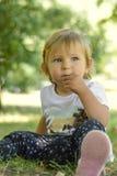 Bebé de un año lindo que se sienta en hierba en parque Imagen de archivo libre de regalías