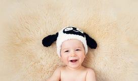 Bebé de un año que miente en sombrero de las ovejas en las lanas del cordero Imagenes de archivo