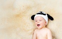 Bebé de un año que miente en sombrero de las ovejas en las lanas del cordero Fotografía de archivo