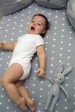Bebé de un año que miente en una cama redonda Imagen de archivo libre de regalías
