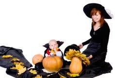 Bebé de Víspera de Todos los Santos con pumpking cercano de la madre Fotos de archivo libres de regalías