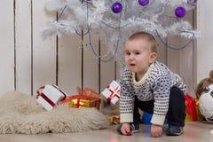 Bebé debajo del árbol de abeto de la Navidad Imagen de archivo
