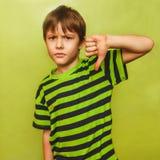 Bebé del adolescente del muchacho que muestra los pulgares abajo en el grande Imagenes de archivo