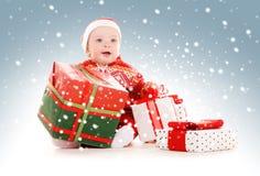 Bebé del ayudante de Papá Noel con los regalos de la Navidad Foto de archivo