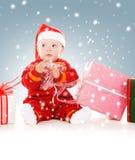 Bebé del ayudante de Papá Noel con los regalos de la Navidad Imagen de archivo libre de regalías