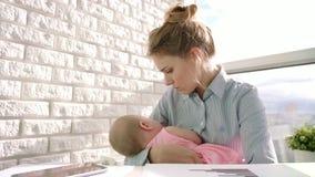 Bebé del cuidado de la mujer de negocios en la ventana ligera Mamá de funcionamiento con el niño en la oficina metrajes