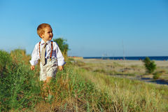 Bebé del estilo del asunto que recorre el campo cerca del mar Imagenes de archivo