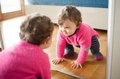 Bebé del niño que juega con el espejo en el dormitorio imágenes de archivo libres de regalías