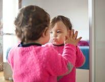Bebé del niño que juega con el espejo en el dormitorio foto de archivo