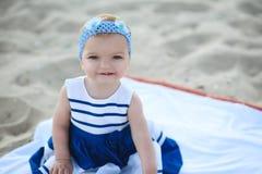 Bebé del ute del ¡de Ð en vestido rayado agradable y la venda azul que se sientan en la arena que sonríe y que le muestra los pri foto de archivo libre de regalías