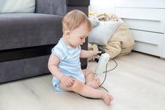 Bebé desatendido que se sienta en piso y que juega con los cables eléctricos Concepto de bebé en peligro imagen de archivo libre de regalías