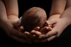 Bebé detenido por las manos de los padres fotos de archivo