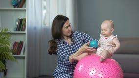 Bebé divertido activo que juega con la bola, desarrollo temprano del niño en casa metrajes