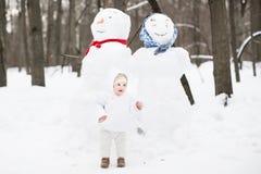 Bebé divertido al lado de un muñeco de nieve en un parque del invierno Imágenes de archivo libres de regalías