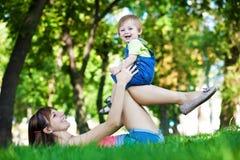 Bebé divertido con la mama en un parque del verano del greenl Imágenes de archivo libres de regalías
