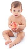 Bebé divertido con la manzana que se sienta en el piso. Foto de archivo libre de regalías