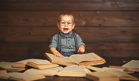 Bebé divertido con los libros en vidrios imagenes de archivo