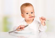 Bebé divertido con un cuchillo y una bifurcación que come la comida imagenes de archivo
