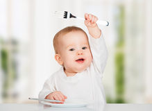 Bebé divertido con un cuchillo y una bifurcación que come la comida