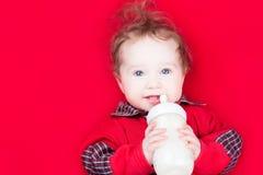Bebé divertido con una botella de leche Imágenes de archivo libres de regalías