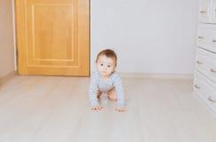 Bebé divertido de arrastre dentro en casa Fotos de archivo