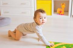Bebé divertido de arrastre dentro en casa Imagen de archivo