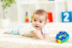 Bebé divertido de arrastre en piso en casa Foto de archivo libre de regalías