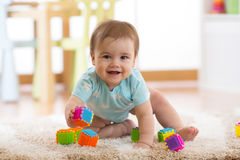 Bebé divertido de arrastre en piso en casa Imagenes de archivo