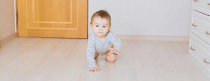Bebé divertido de arrastre lindo dentro en casa Imagenes de archivo