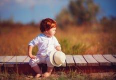 Bebé divertido del niño del pelirrojo que se sienta en la trayectoria de madera en el campo del verano Foto de archivo