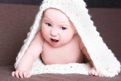 Bebé divertido en el arrastre de lana blanco de la bufanda Imagen de archivo libre de regalías