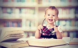 Bebé divertido en vidrios que lee un libro Imagenes de archivo
