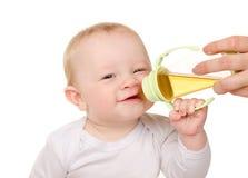 Bebé divertido que bebe de la botella Fotos de archivo