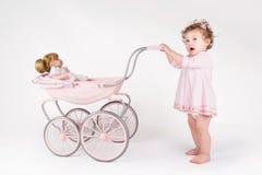 Bebé divertido que camina con un cochecito de la muñeca Fotos de archivo