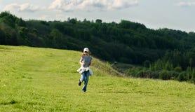 Bebé divertido que corre en campo verde Fotos de archivo libres de regalías