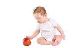 Bebé divertido que juega con una manzana roja grande, aislada en blanco Foto de archivo libre de regalías