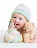 Bebé divertido que miente en cama con el juguete de la felpa Foto de archivo libre de regalías
