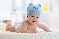Bebé divertido que miente en el estómago en cama en sala de estar Imagen de archivo