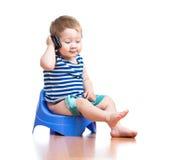Bebé divertido que se sienta en el crisol de compartimiento con pda imagen de archivo libre de regalías